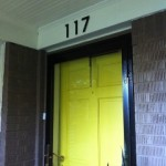 Citron Door on a Mid-Century Modern Home. Blink Contemporary House Numbers mounted above door.