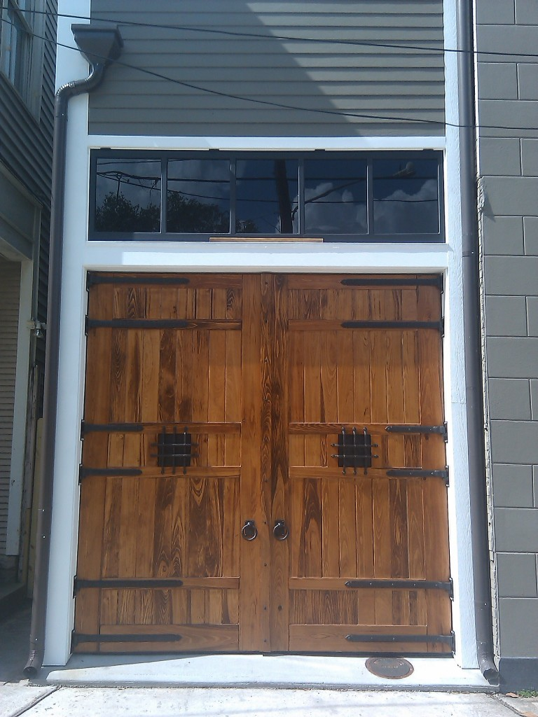 New Orleans historic carriage house doors with dark bronze hardware adorning it, custom wood doors